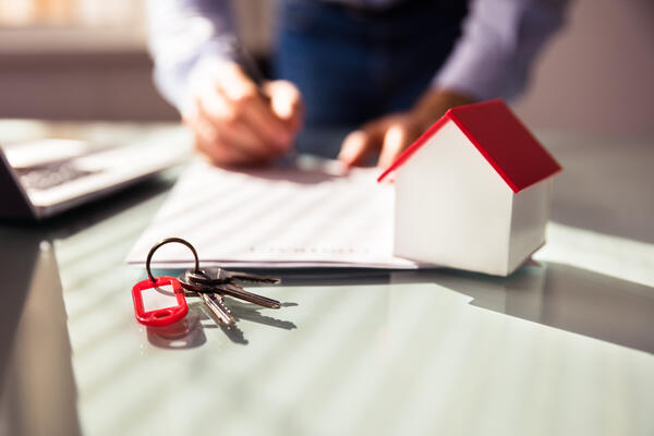 Close-up Of House Model And Key Near Human Hand Signing Contract