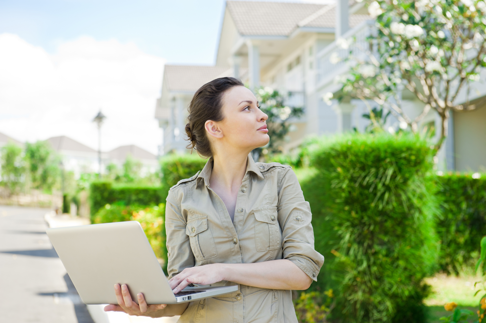 Young businesswoman (real estate agent) holding a laptop and presenting detached family house